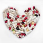 Medication capsules and pills in shape of heart on white background, top view